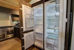 The kitchen features large fridge and a fridge/freezer.